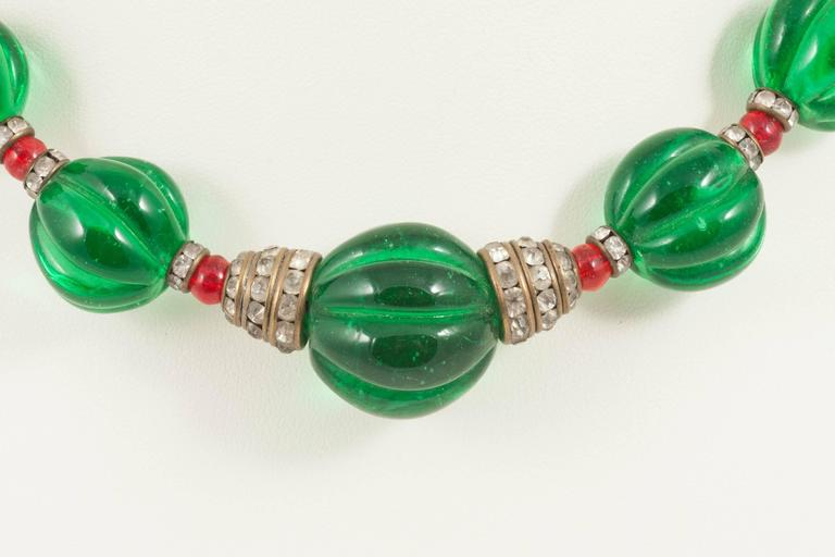 A shorter, very wearable graduated necklace made by Maison Gripoix for Chanel in the late 1930s. Poured glass melon cut emerald beads are interspersed with several rows of small poured glass ruby beads, and characteristic paste rondelles. This