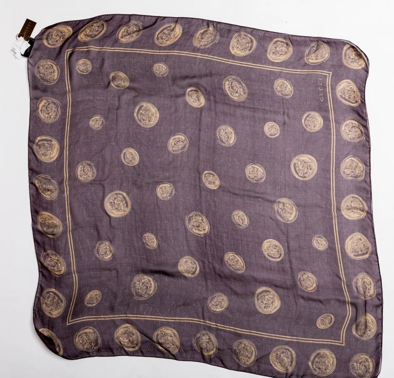 Wonderful vintage Gucci scarf in aubergine with gold coins featured throughout. This scarf has never been used and its original Gucci tags are still attached.