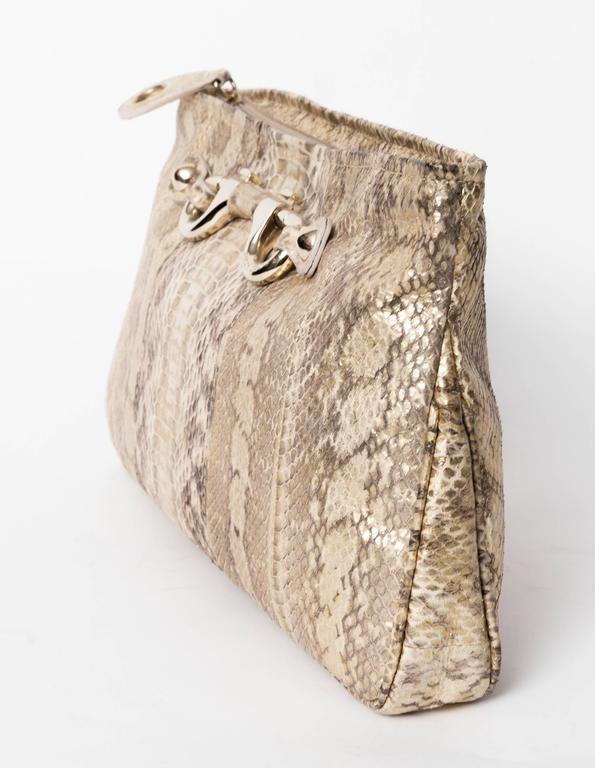 Jimmy Choo Gold and Tan Snakeskin Clutch with Silver  Horsebit Detail. Closes with a zip ending in a snake tab pull.  Lining is a gold grosgrain ribbon with one flap pocket. There are makeup stains to the lining.