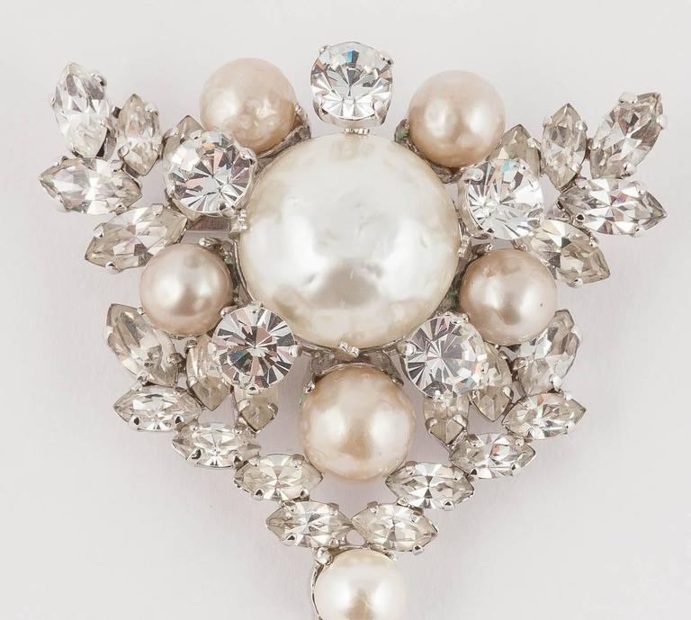 This is a pristine Dior brooch made in Germany by Henkel and Grosse in 1961. It has a wonderful leaf like paste frame for the hand set and dangling baroque pearls.  It would be a brilliant starting point for a wedding dress. Equally it would look