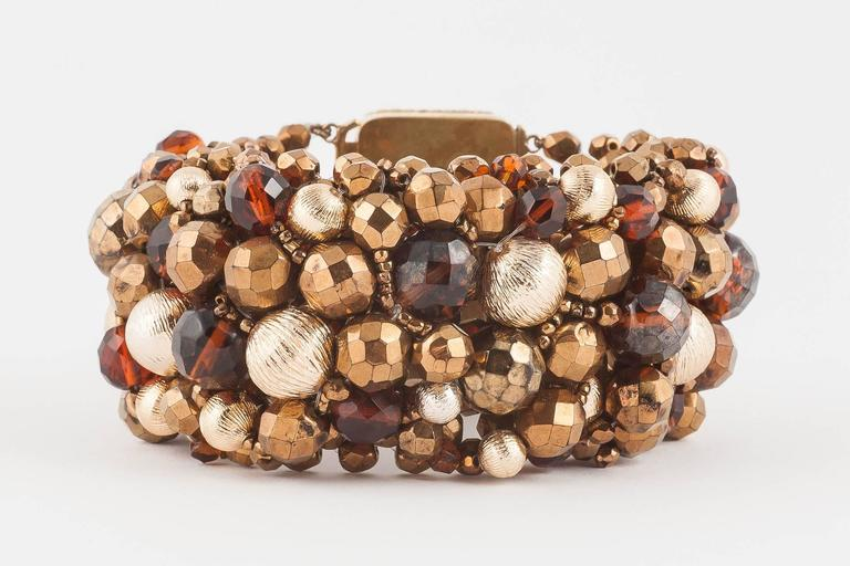 A dynamic and strong Coppola e Toppo beaded bracelet from 1964, in bronzes, browns and golds, a rich mix of Bohemian half-crystal beads and brushed gilded metal ;boules' or beads,all mounted on a web of more beads, with a large beaded signature