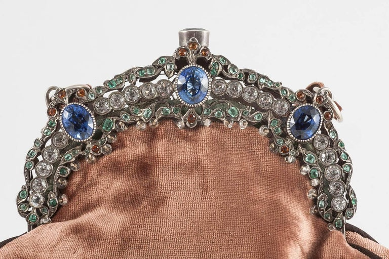 A gently, elegantly curved frame is set with white spinels, citrines, emeralds and synthetic sapphires, in a frame of silver, with the reverse of the frame being engraved and hand worked, crowns a silk velvet bag. The bag is highlighted with small