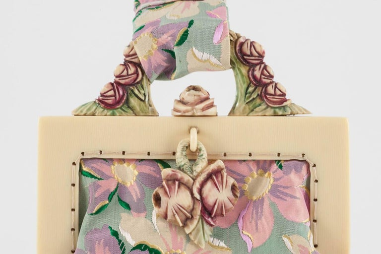 An exquisite and unique little handbag, with a carved Bakelite and hand coloured frame, in a stylised floral motif, with a beautifully coloured silk 'floral' fabric bag. Lined in chartreuse silk with a delicate silk 'floral' trim, it has a secure