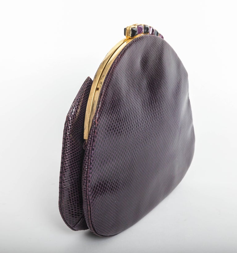 Gorgeous Judith Leiber eggplant clutch with gold chain shoulder strap. Amethyst and onyx cabochons adorn the top of this bag. Excellent condition.