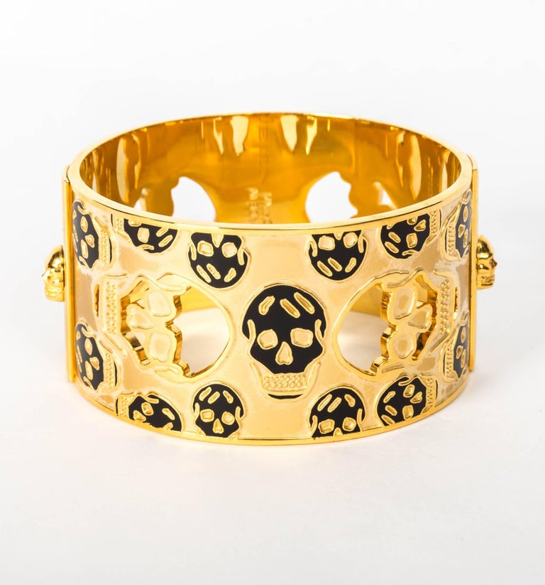 Fantastic Signed Alexander McQueen Matt Gold Cuff Embellished with Black Enamel Skulls The sides of this cuff have protruding skulls enhancing Alexander McQueen's iconic skull motif. Diameter is 2 1/2 inches with a circumference of 8 3/4 inches.