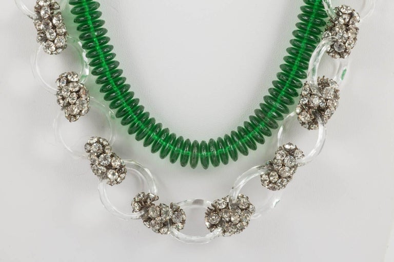 A magnificent long beaded necklace, made from 'doughnut' shaped emerald green glass discs, faceted clear glass rings, of two sizes, and clear paste clusters. With an engraved barrel clasp to the rear (marked 'Made in France'), the emerald discs form