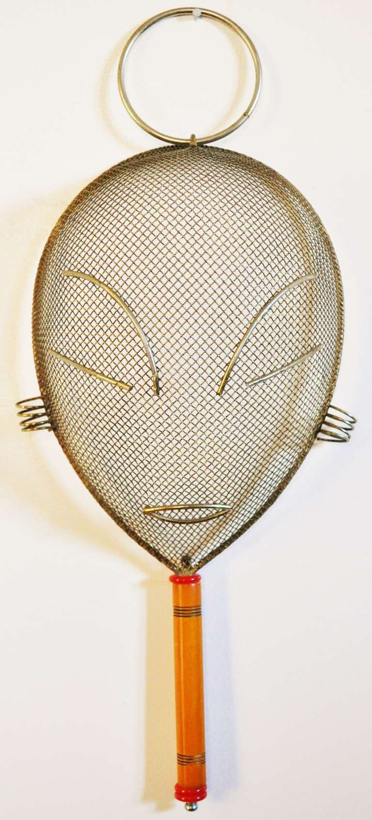 This Mid-Century wire wall mask by Frederick Weinberg features the usual large ring at the top but also a seldom seen handle made from incised butterscotch Bakelite with red Catalin accents. This item is in near mint condition.