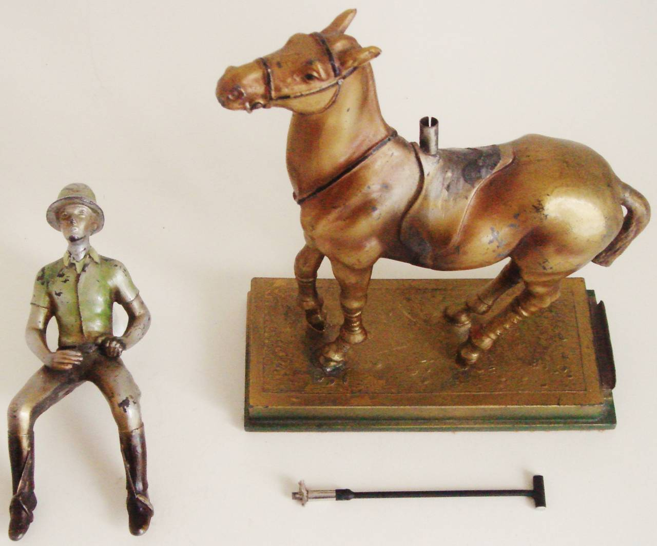 This rare Austrian Art Deco figural table lighter is in cold painted spelter (zinc alloy) and takes the form of a mounted polo player. The rider's polo mallet can be withdrawn from the pommel of the rider's saddle to reveal the striker wand and the