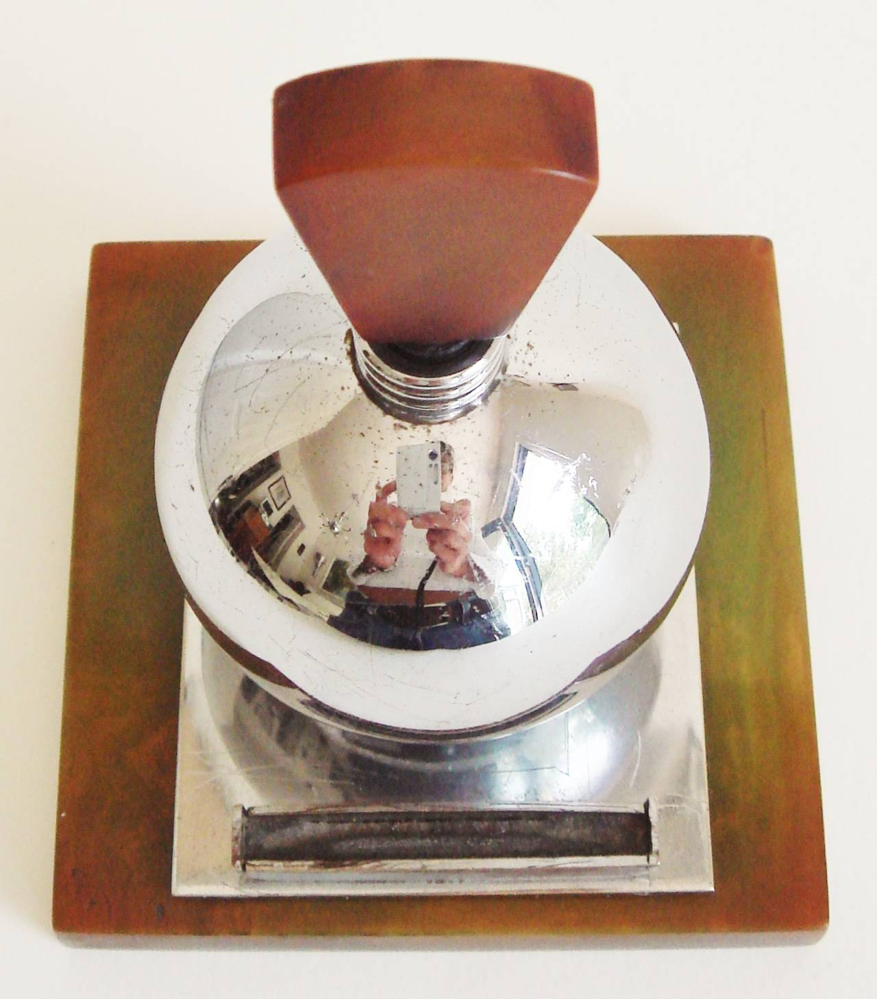 The Bakelite base and keystone wand finial of this rare English Art Deco chrome spherical striker lighter would originally have been a marbled leaf green but in 80+ years the colour has developed a marvelous and rich treacle-toffee patina. The
