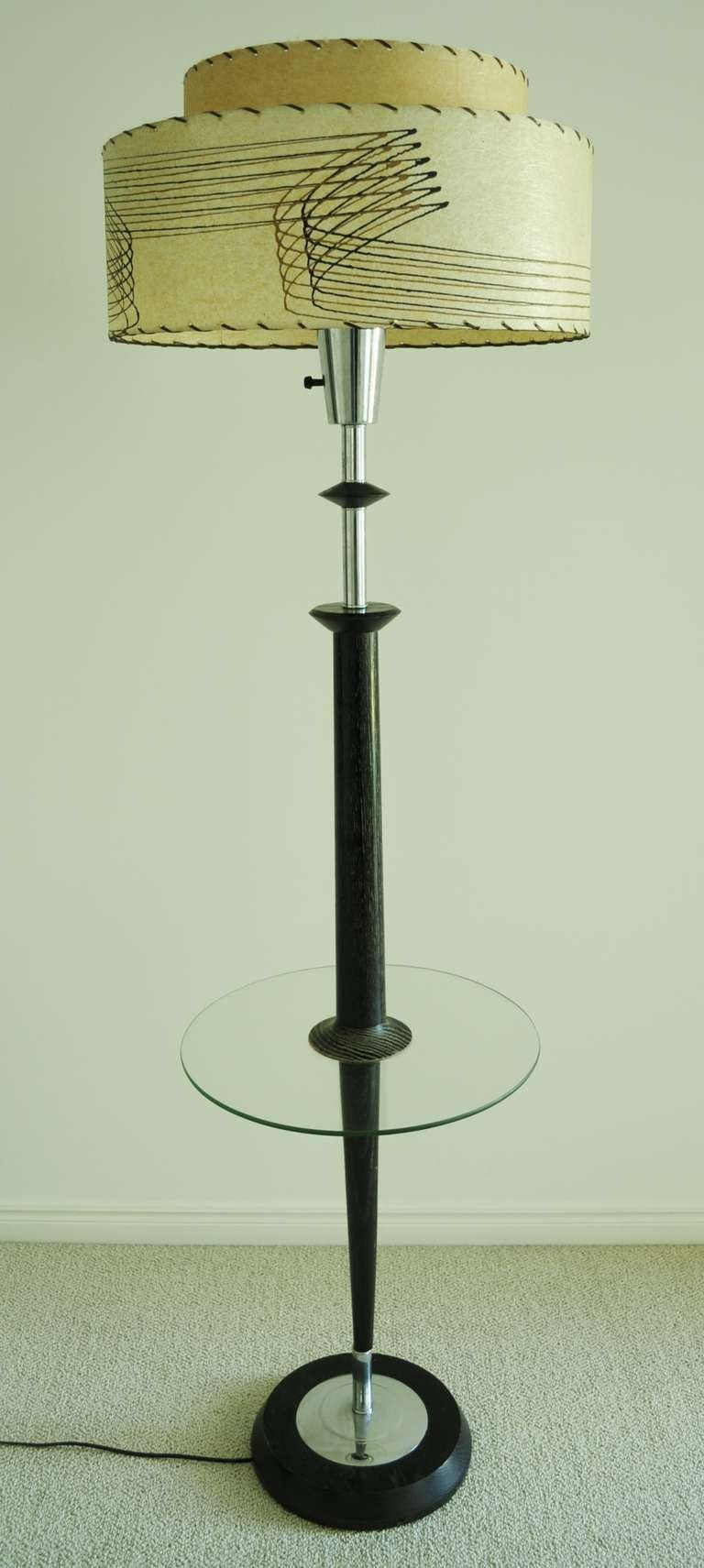 This fabulous American Mid-Century Modern, black cerused oak  floor lamp with chrome accents, original glass reflector and thick circular glass integral table by Majestic is near mint. The original two-tier fiberglass shade is in perfect condition,