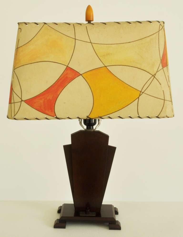 This bold Art Deco 'Outsider-Art' lamp with its keystone form sits on a stepped base and the whole is constructed from laminated burgundy/brown Bakelite sheets. The base has an aluminum and Bakelite switch on the foot and is topped with a