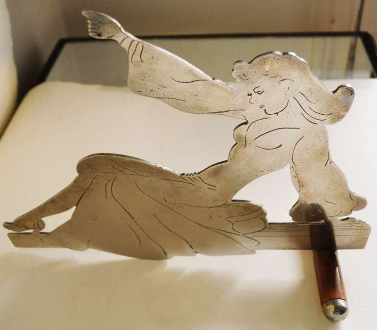 This very rare and relatively large art watch stand is probably an Outsider or Trench Art piece. It is in the form of a cut-out of Norman Pett's famous glamour-girl/pin-up, Jane who starred in her eponymous comic strip in England's Daily Mirror