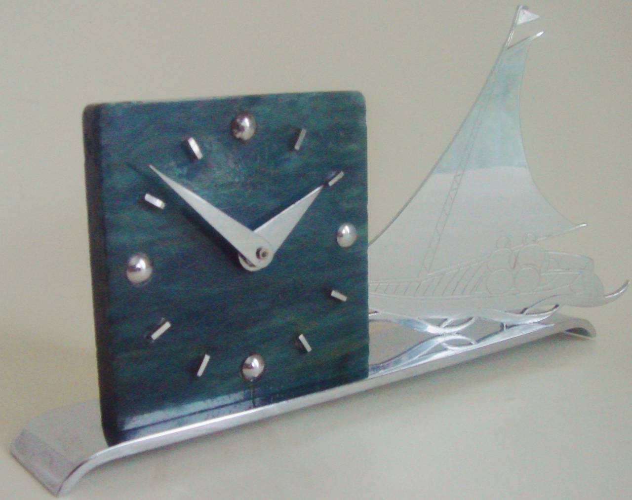 The body of this distinctive Art Deco mechanical shelf clock is made in a sea blue/green  marbled form of milk based French plastic that is known as Galalith or in the UK, Erinoid. It has a very geometric face with both dome numerals and hands in