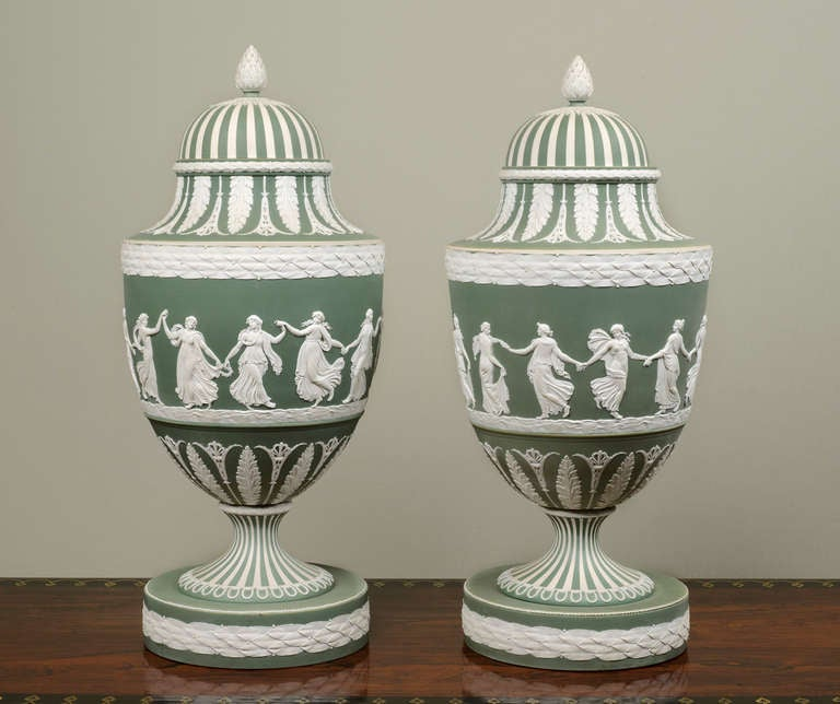 Each Vase is decorated with one of the best-known of all the Wedgwood reliefs, the Dancing Hours, which are attributed to John Flaxman, the finials are in the form of artichokes, the bases are applied with laurel bands Provenance: Viscount Cowdray