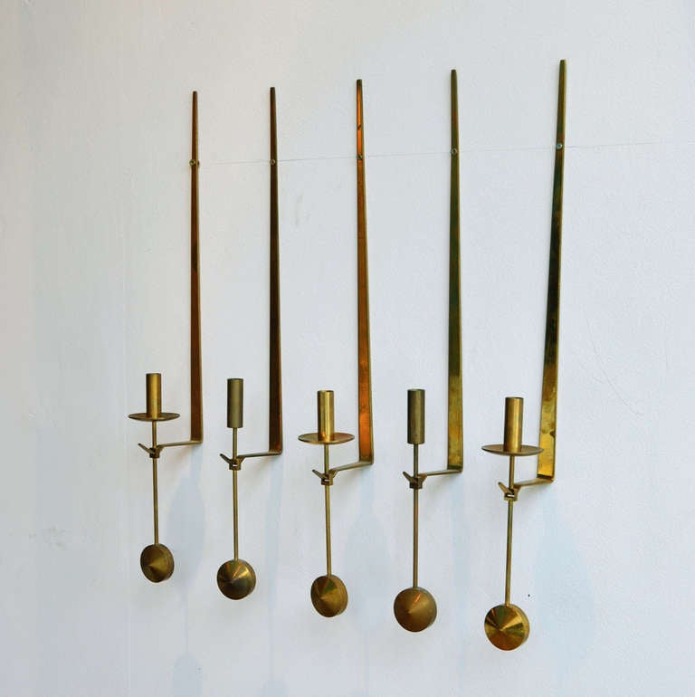 A Set of @three' wall mounted brass candle holders balancing in an upright position by round brass weight. Beautiful craftsmanship Manufactured by Skultuna Messingsbruk. Set of three are available; the left-middle-right ones, with  a tray