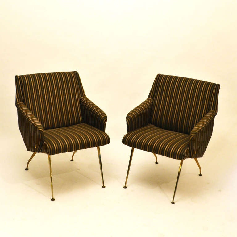 Elegant & compact French lounge chairs reupholstered luxurious in black and gold striped fabric and on fine brass legs. These stylish chairs give great comfort and support.
