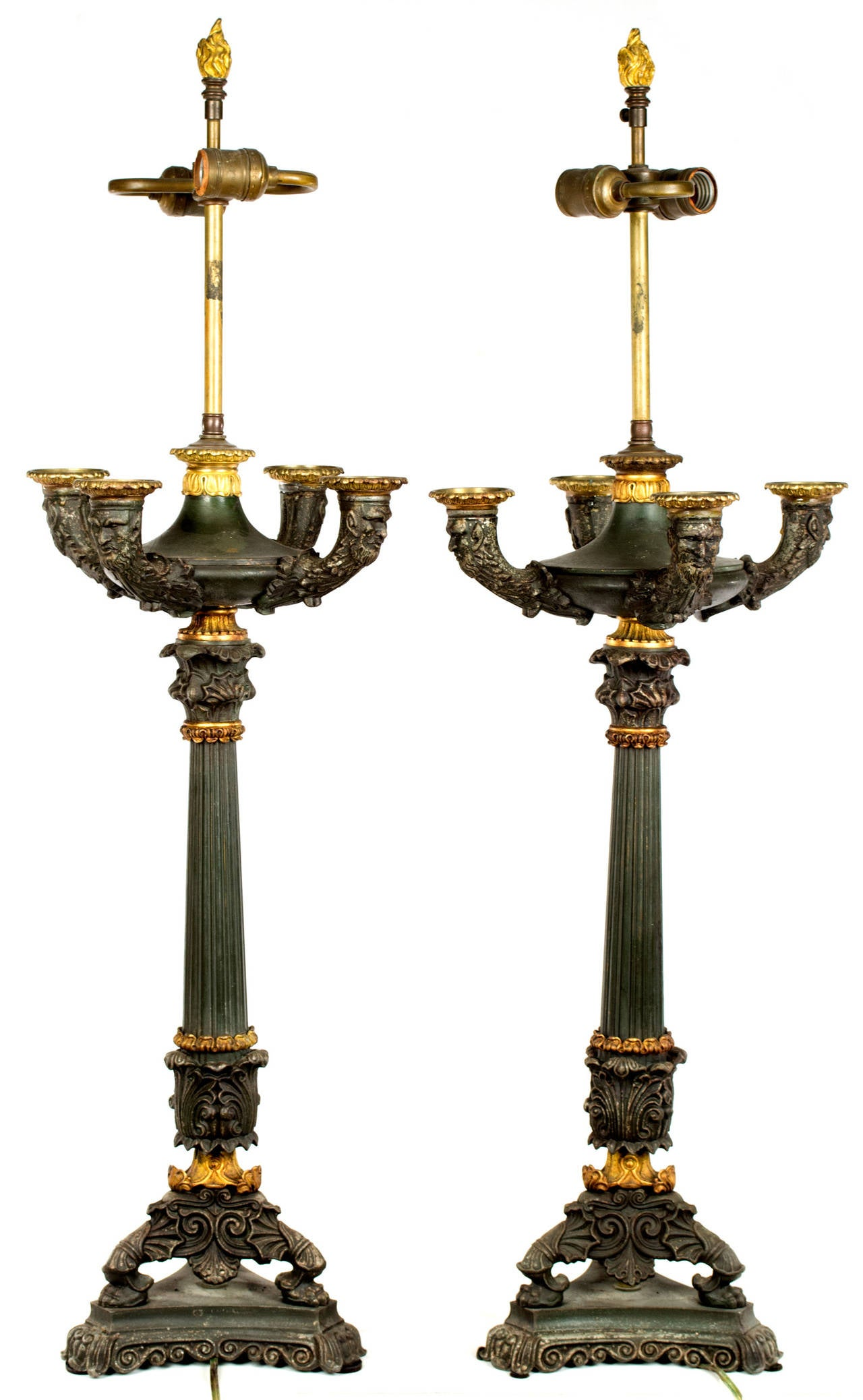 Two lamped bronze Renaissance revival candelabras, each with four arms terminating in masks topped with gilt bronze bobeches. The arms sit atop a fluted column decorated with acanthus leaves and standing on three legs atop a pedestal.