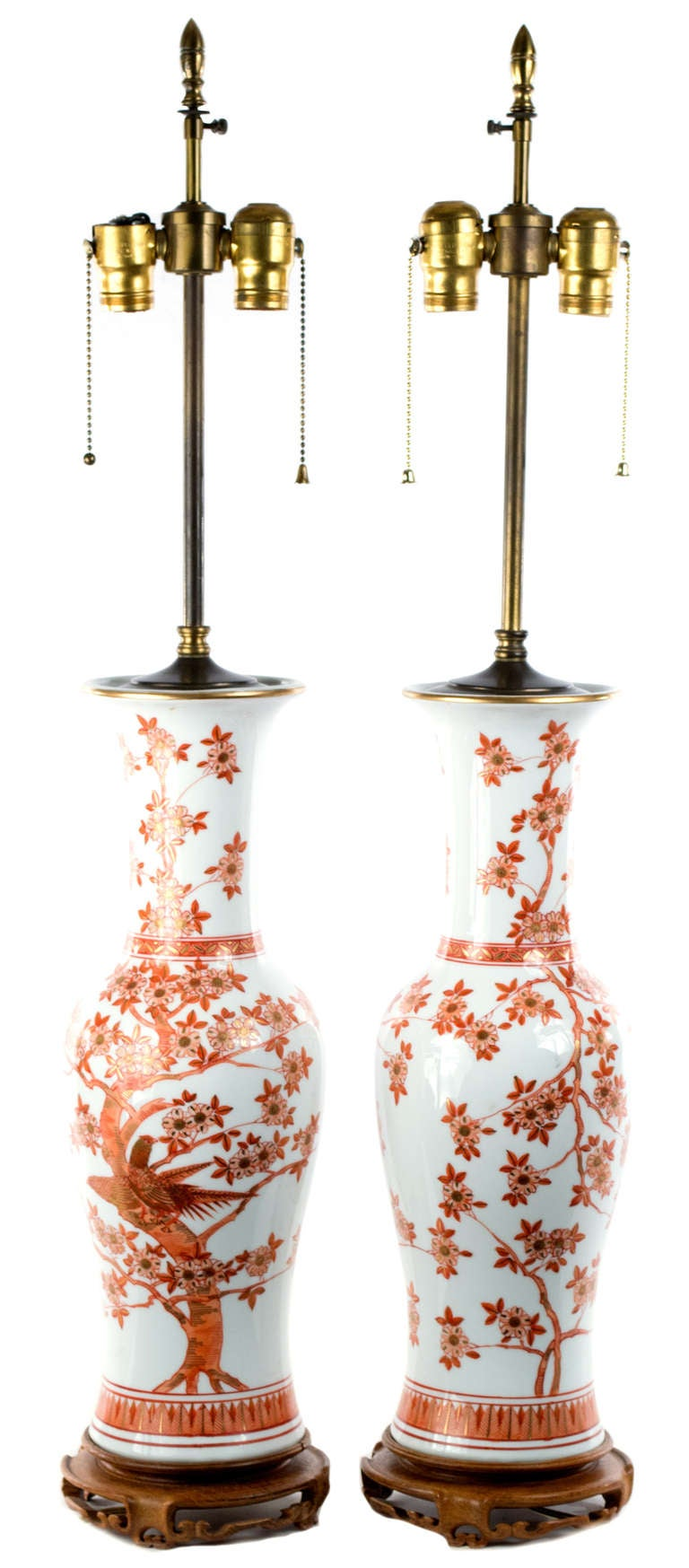 Placed on a wood stand and fitted with working brass lighting elements and silk shades,  each baluster vase features virtuosic gilt and red underglazed paintings of exotic birds among cherry blossoms.