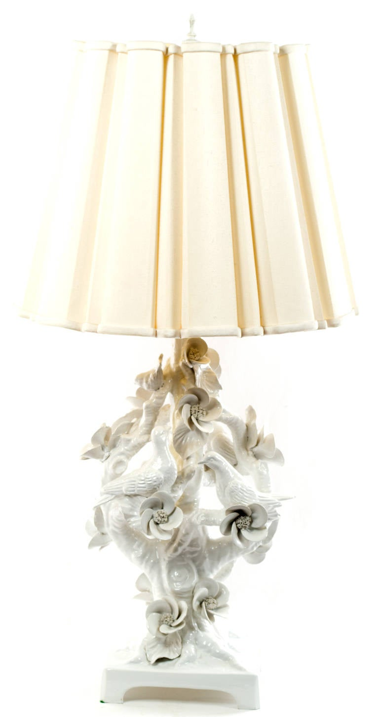 Featuring full-relief figures of doves resting in blooming branches, this lamp was made in Italy during the 1940s and is fitted with a brass harp and silk shade.