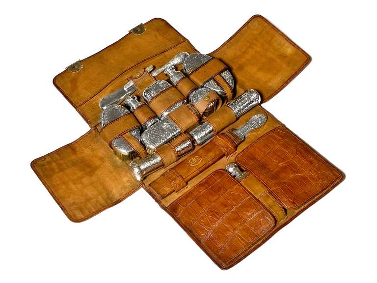 In genuine crocodile skin case with the initials C.H. discretely imprinted on the front.  Antique sterling silver pieces inside include hairbrushes, hip flask, manicure set, soap dish, clothes brush, shoe horn, penknife, assortment of bottles and