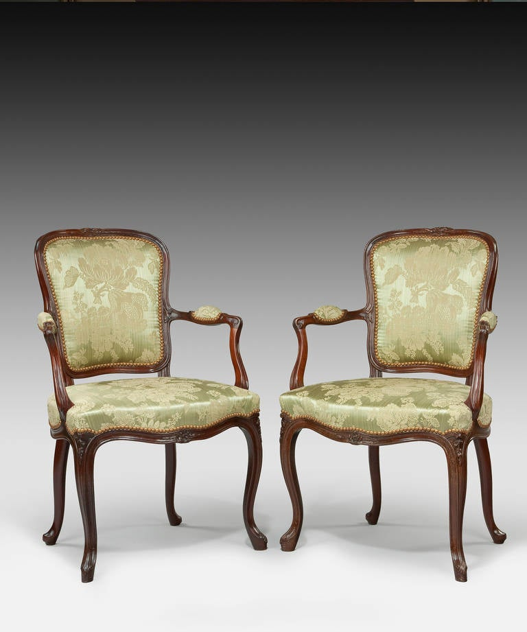 A pair of George III Hepplewhite period mahogany salon armchairs; the carved mahogany show-wood frames having outscrolling arms and standing on elegant cabriole legs.