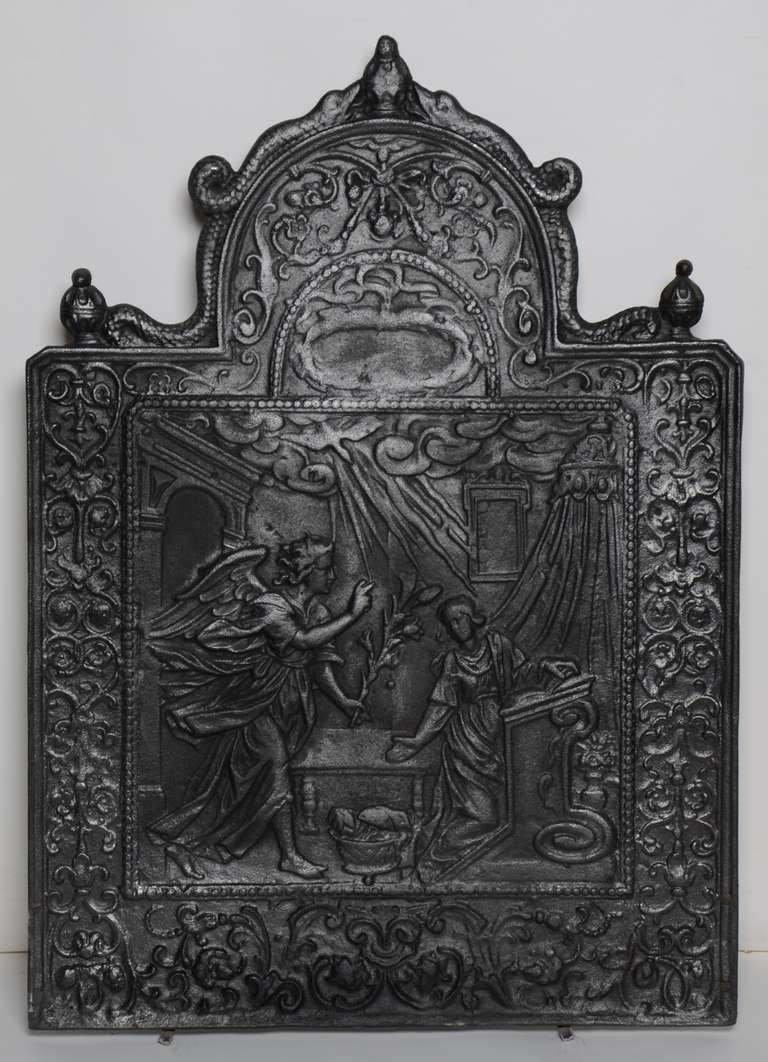 This large and rare fireback displays the Annunciation -  the Christian celebration of the announcement by the angel Gabriel to the Virgin Mary that she would conceive and become the mother of Jesus, the Son of God, marking his Incarnation.