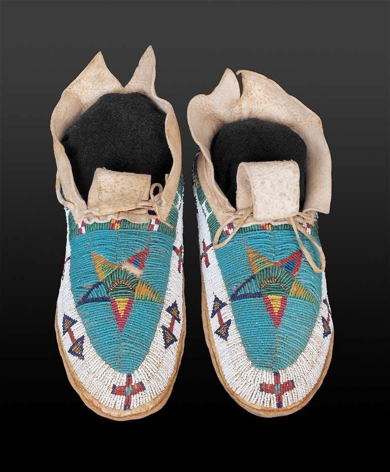 Constructed of native tanned hide, these moccasins were intricately beaded in a pictorial design consisting of star, cross and arrow motifs in glass trade beads.