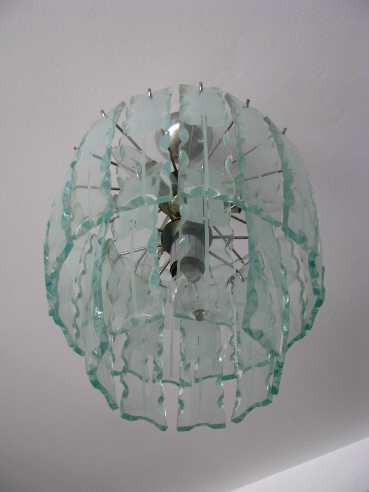 Italian 1960s chandelier with bold Fontana Arte style 25 thick slabs of partly frosted glass, each 24cm (9.5 in). Each of these slabs is hand-cut and hand-chipped. Holds four bulbs.  Measures:  Height 19.7 in. (50 cm). Diameter 13.8 in. (35