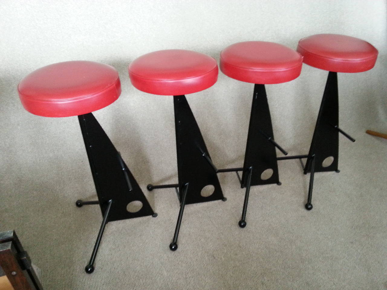 Four iron bar stoolsstyle of Mathieu Matégot, France 1950, black laquered iron, upholstery in red vinyl in perfect vintage condition.  Measures: Height: 32.7 in (83 cm) Seatdiameter: 14.2 in (36 cm) Width: 18.2 in (46 cm)  Note: Rare set, stunning