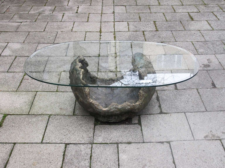 Exceptional coffee table with a bronze base and oval glass top in the style of Paul Evans.