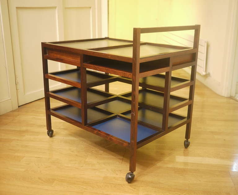 A rare serving trolley designed by Bodil Kjaer for her apartment in 1959. Solid rosewood and rosewood veneer, bleu formica, on castors and stainless steel hot plat. Hidden box. Fully original.
