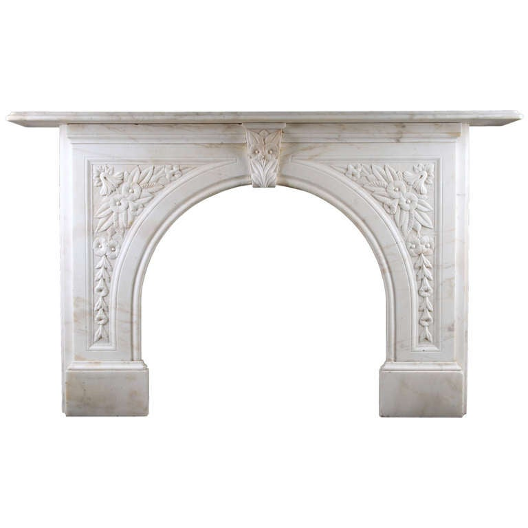 an antique victorian arched fireplace surround in white