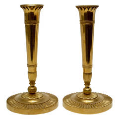 A pair of French empire gilt bronze candlesticks, early 19th century.