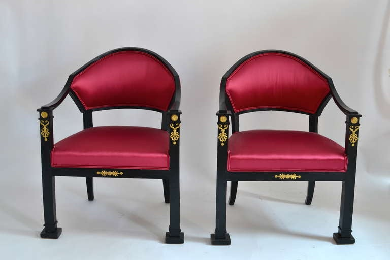 A pair of Swedish ebonized Empire armchairs with gilt bronze mounts. The model is derived from an earlier Gustavian design. Made in Stockholm, circa 1820. If needed there is a total of six chairs available. A very elegant set.