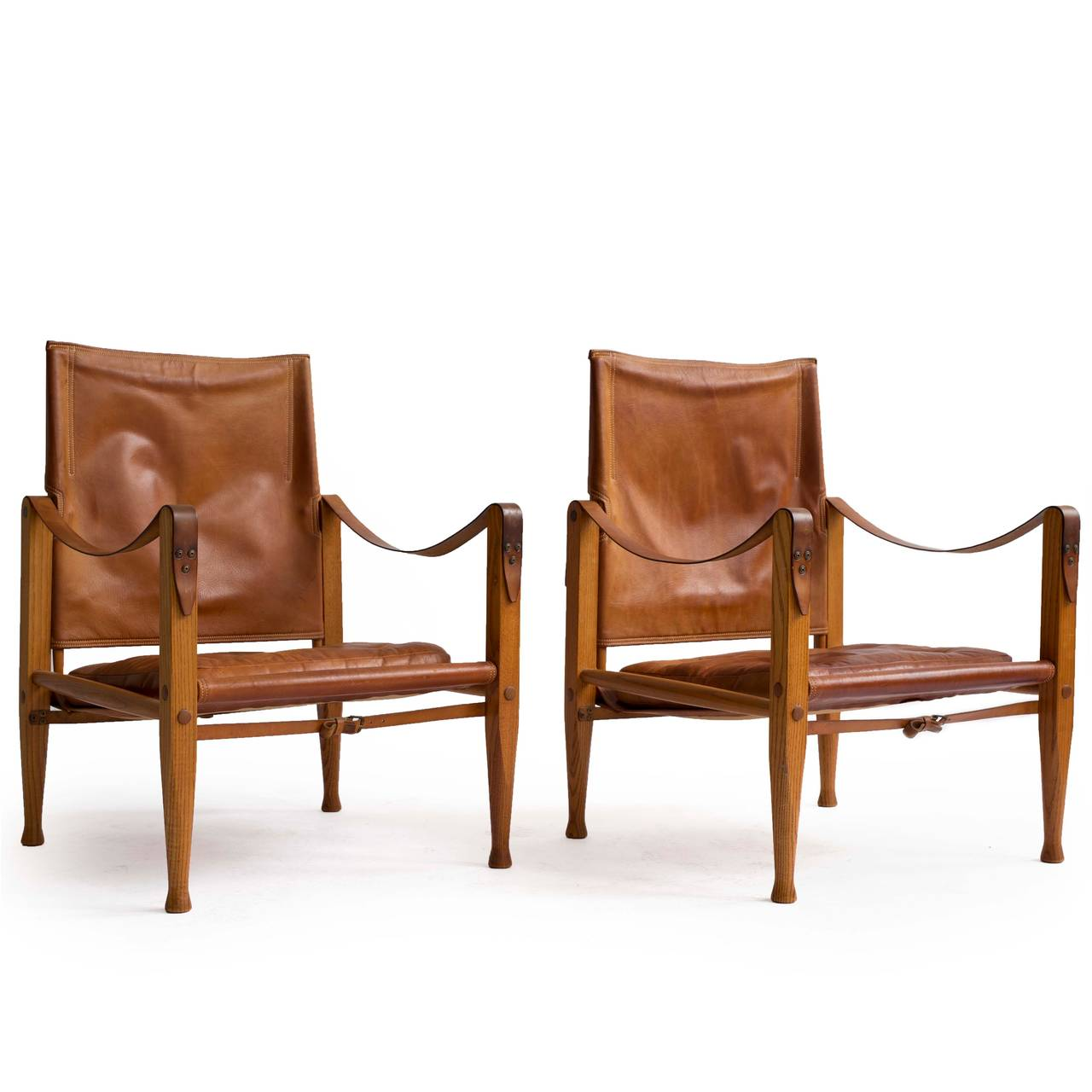 A pair of Kaare Klint 'Safari chairs' with ash frame, upholstered with original patinated natural leather.   Designed by Kaare Klint 1933, manufactured by Rud. Rasmussen, Copenhagen, Denmark.   Very well preserved original condition.