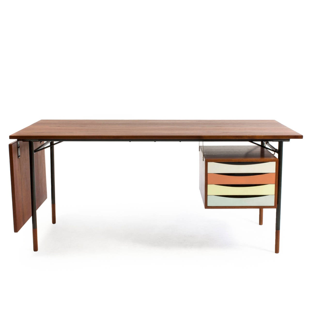A rare freestanding Finn Juhl teak desk with colored drawers and detachable flip-down leaf.   Drawer section, tabletop and shoes of teak, frame of gunmetal.   Designed by Finn Juhl 1953 and manufactured by Bovirke, Denmark, model BO 69.   Burn