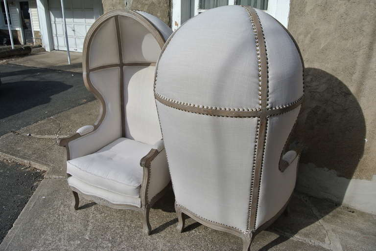 Beautiful pair of Rustic French canopy hood bishop's chairs. Faded wood frame with newly reupholstered in white linen with brass tacks.