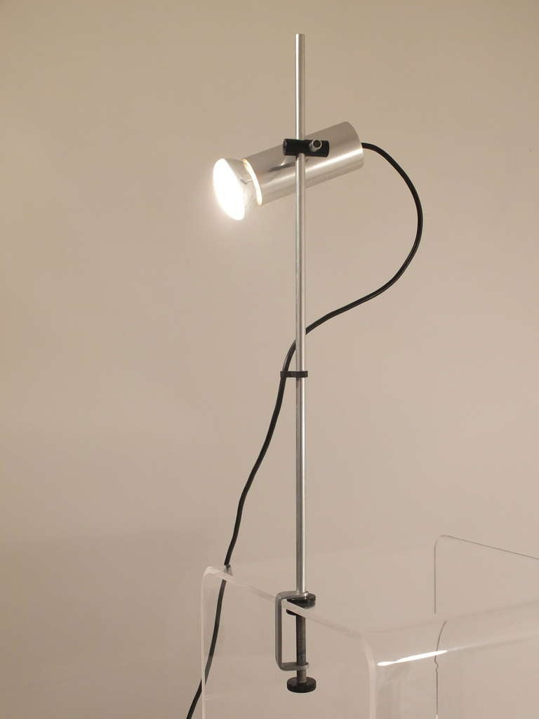 An engineered clamp lamp in aluminum with an adjustable spot light in a cylindrical form that tilts for uplighting or downlighting and moves up and down the pole for height adjustments. By Peter Nelson for Architectural Lighting, English, circa 1970.