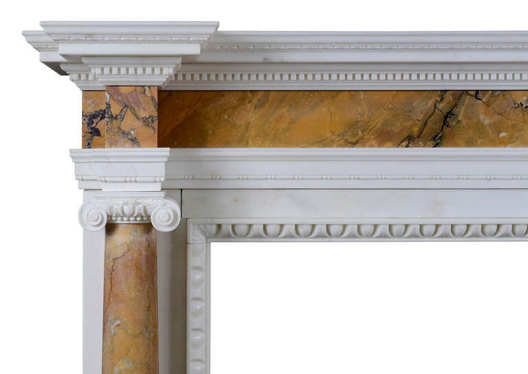 A medium scale George II English Siena and Statuary marble fireplace with columns. The carving of fine quality including leaf moulding and dentils to shelf, egg and dart inner moulding. The frieze and columns of Siena marble, mid-18th century. An