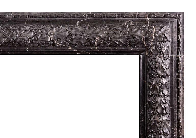 An elegant and understated Nero Marquina bolection moulded fireplace with carved oak leaf decoration and cross banded centre ribbon. A copy of a period original. Could be made to any size in various materials if required.  Shelf width - 1403 mm