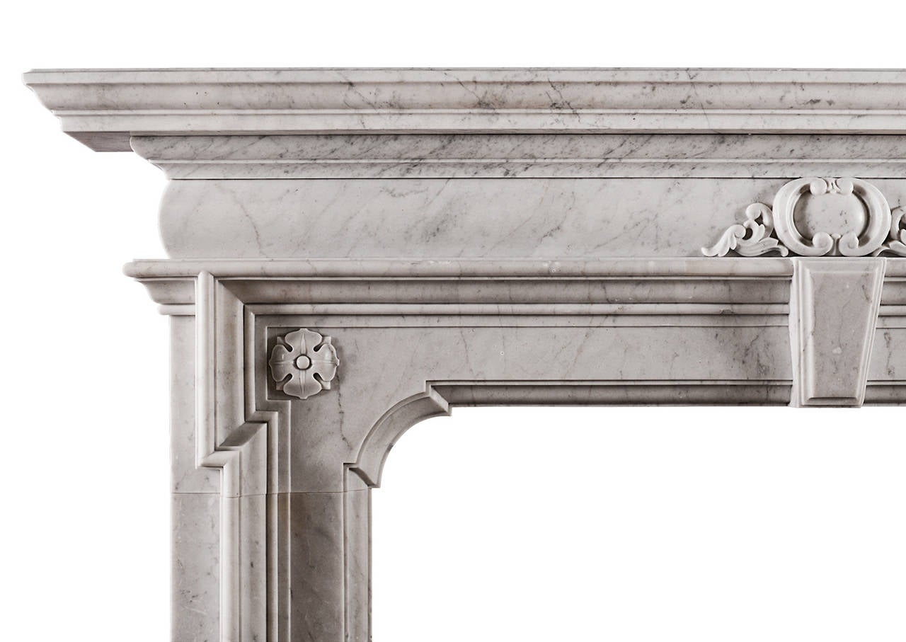 A striking marble fireplace in Italian Carrara marble. The moulded jambs with carved rosette to top, the barrel frieze with carved cartouche to centre and key stone below. Shaped moulded cornice shelf above. A fusion of styles including Tudor and