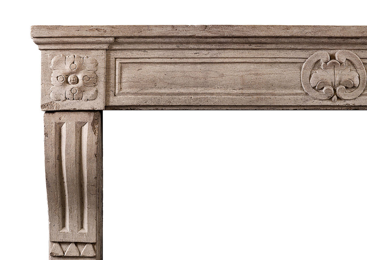 An attractive petite period Louis XVI stone fireplace. The shaped jambs with stop flutes to base, the panelled frieze with cartouche to centre with carved square rosette end blocks. Moulded shelf above. A rustic piece from a wine house in Beaune.
