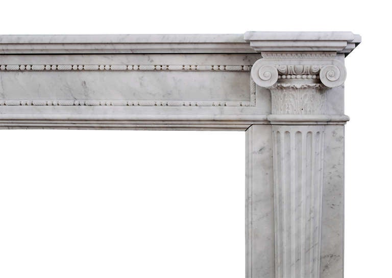 A very finely carved French Louis XVI in Carrara marble. The panelled frieze with delicate pearl and string beading, scrolled ionic capitals and leafwork to end blockings. The jambs with tapering fluted columns with carving to middle. Breakfront