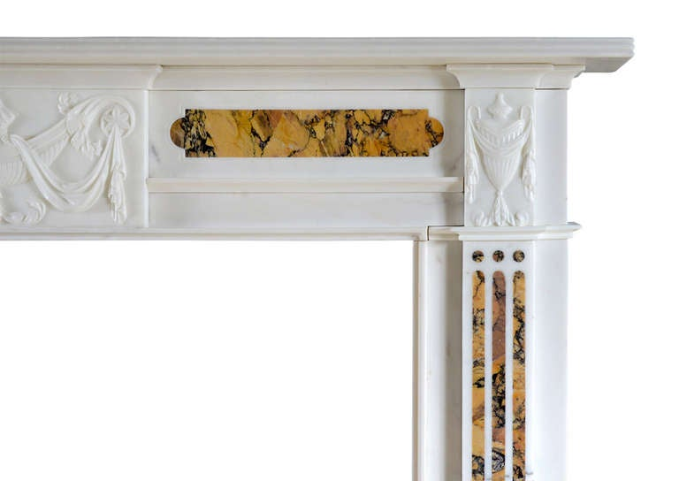 A good quality late Georgian statuary and Siena marble fireplace. Finely carved urn to centre tablet with flowing drapery and foliage. The fluted jambs surmounted by similar carved urns and drapery, and shaped panels to frieze inlaid with Siena.
