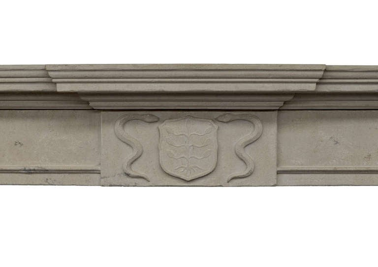 A 19th century English limestone fireplace, with armorial shield to centre, flanked by serpents, plain moulded frieze with tapering pilasters to jambs, and moulded breakfront shelf.  Measures: Shelf length 68.75 in / 1746 mm Overall height 55 in