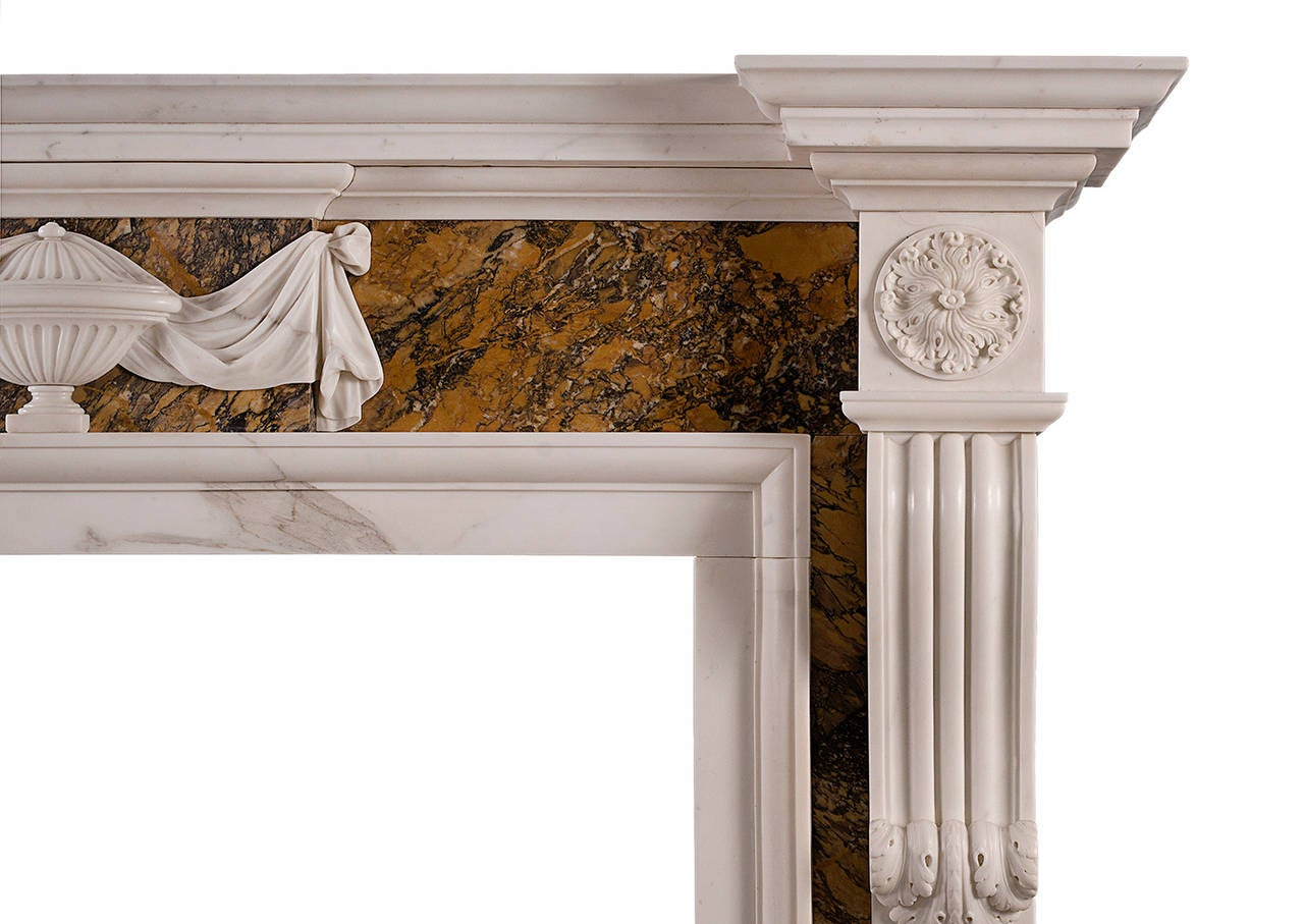 An English, Georgian style fireplace in statuary marble with Siena inlay. The panelled jambs with carved brackets, surmounted by carved end blockings. The Siena marble frieze with centre blocking featuring urn with cascading drapery. Moulded shelf