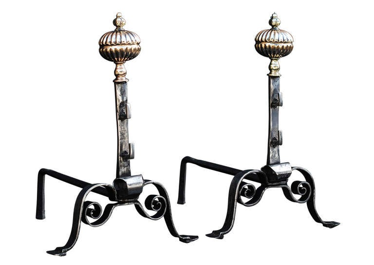 A pair of 18th century, English polished wrought iron firedogs. The scrolled feet surmounted by gunmetal fluted shaped finial and engraved brass mask top. Good quality.