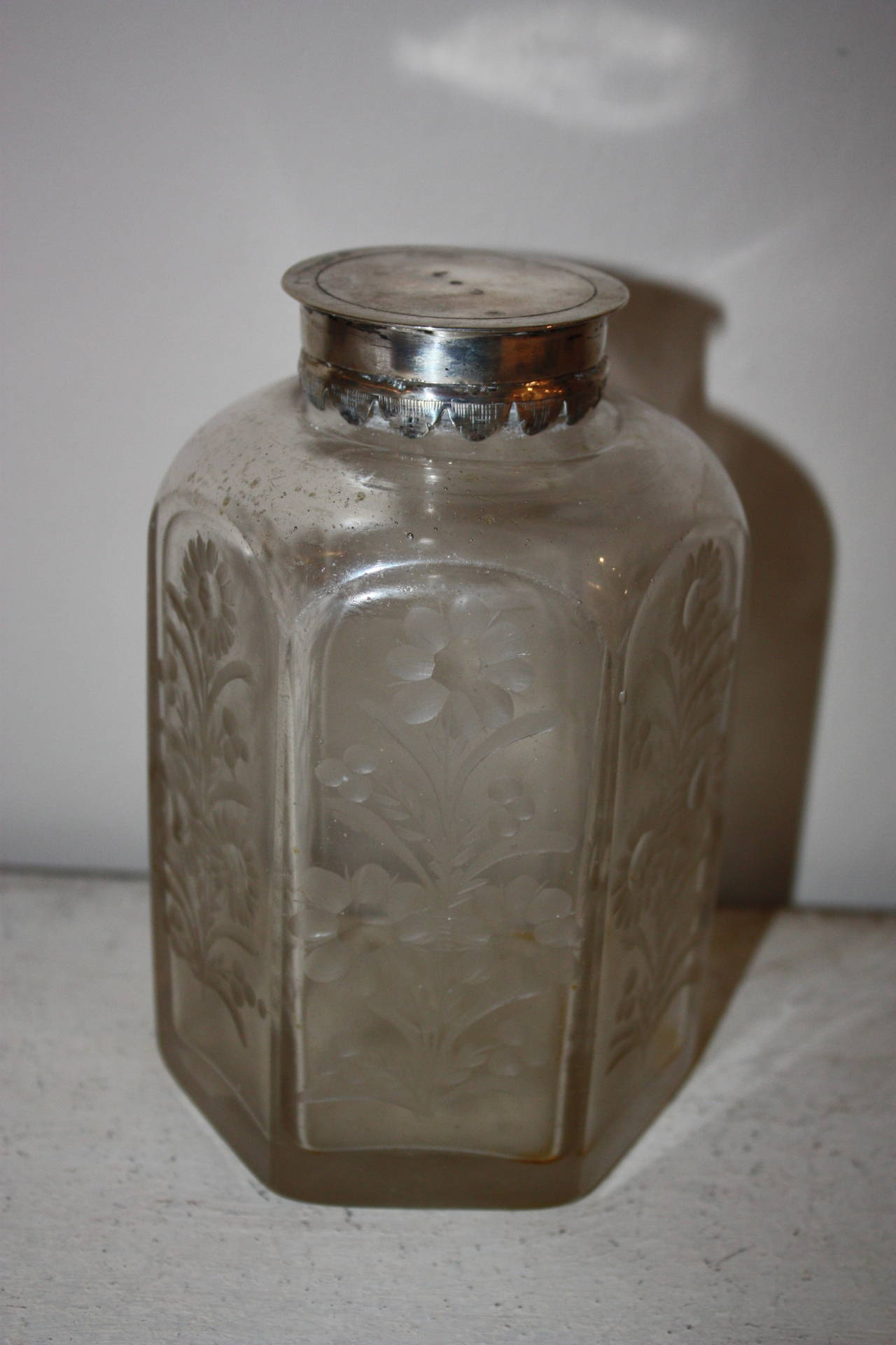 Very beautiful glass bottle with silver lid and engraved flower motives.