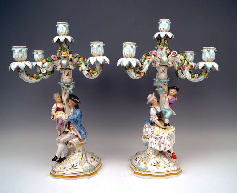 Each of the candlesticks has  FIVE grommets /  there are FIVE ARMS existing, being abundantly decorated with sculptured flower's blossoms and fruits. - The stalk consists of SCULPTURED PAIR OF FIGURINES - these are:   - a lady having sat down,
