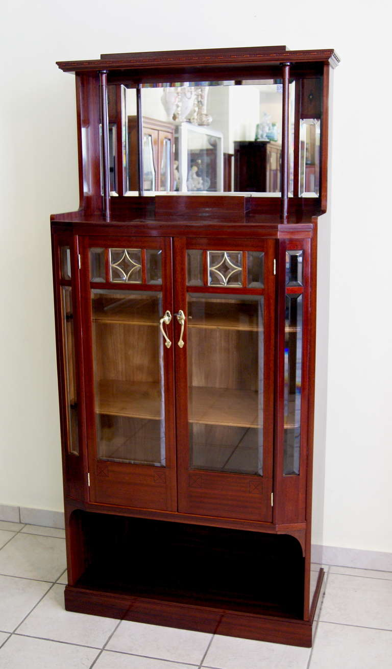 Art Nouveau Viennese Vertiko glass cabinet with glass doors    made  circa 1900  Mahogany veneer  Refurbished by hand  Most elegant appearance    This furniture piece consists of following parts:   1.  TOP PART       a backplane is existing to which